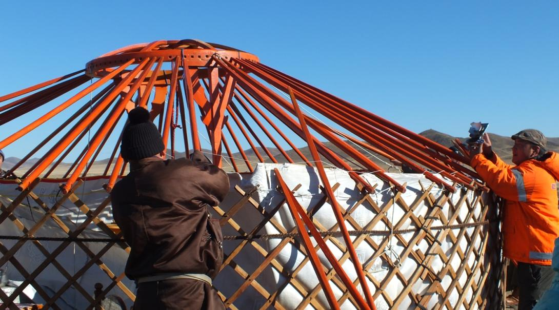 モンゴル遊牧民のテント式移動住居ゲルの建設を手伝うボランティアたち
